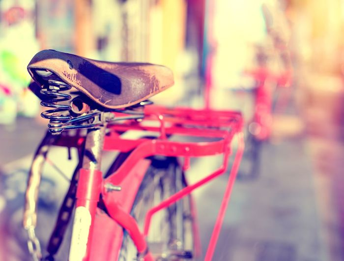 Detail of a Vintage Bicycle Seat Resting in the city Street (vintage color toned image) Bicycle Focus On Foreground No People Mode Of Transportation Transportation Close-up Day Handlebar Outdoors City Handle Street Vintage Retro Style Old Red