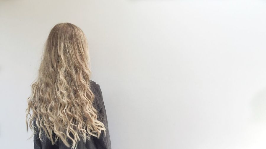 Rear View Of Woman With Blond Hair Against White Background