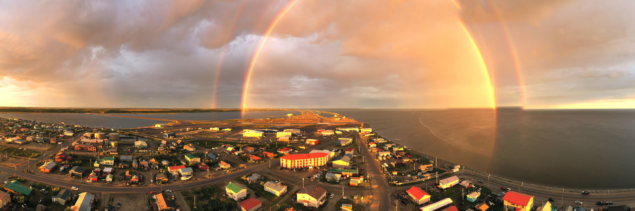 High angle view of rainbow over cityscape against sky during sunset