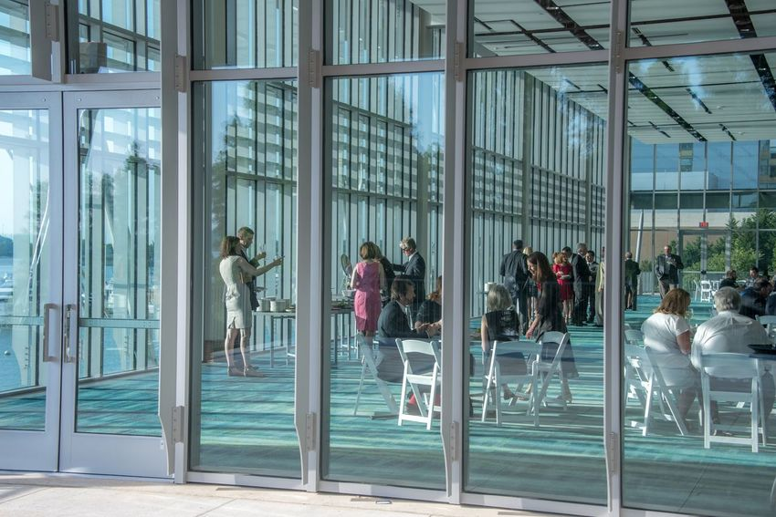 Guests enjoying a reception in glass conference center. Reception Narional Harbor Maryland USA Maryland Conference Event Architecture Glass - Material City Built Structure Building Exterior Reflection Group Of People Transparent Window Business Lifestyles Real People Day