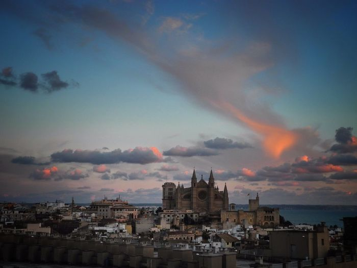 Palma cathedral in city against sky at dusk
