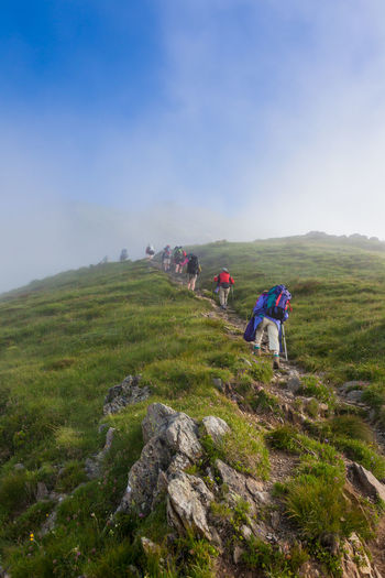 Low angle view of people hiking on hill against sky