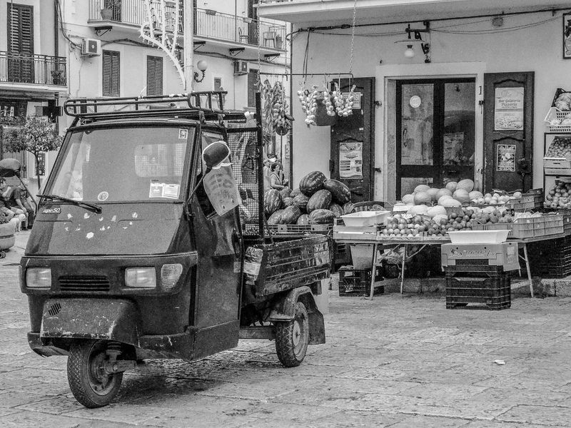 Fruit and vegetable market with small means of transport Architecture Black & White Blackandwhite Blackandwhite Photography Building Exterior Built Structure City Day EyeEmNewHere Food Fruit And Vegetable Fruit And Vegetable Market Fruits Land Vehicle Lifestyles Market Marketplace No People Occupation Outdoors Shop Transportation Tricycle Vegetables Working