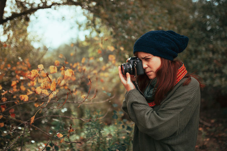 Woman photographing with camera while standing in forest