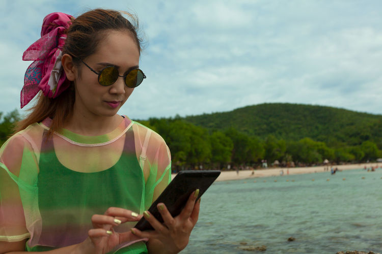 Holiday Thailand Beautiful Woman Casual Clothing Communication Fashion Glasses Hill And Stone Leisure Activity Lifestyles Looking Model Asian Nature One Person Outdoors Real People Sea And Sky Seascape Sunglasses Technology Water Wireless Technology Women Young Adult Young Women