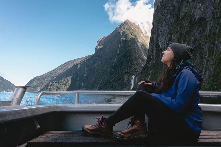 Woman sitting in boat on lake against mountains