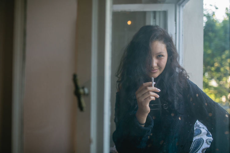 Portrait of woman smoking cigarette by window at home