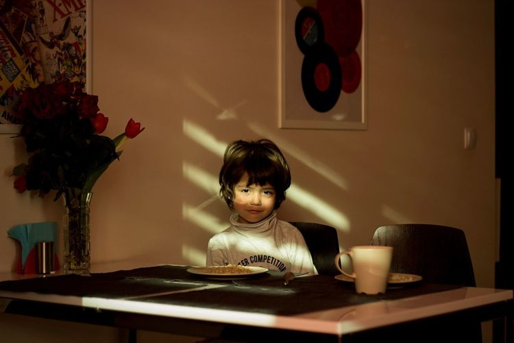 Portrait of boy sitting at dining table