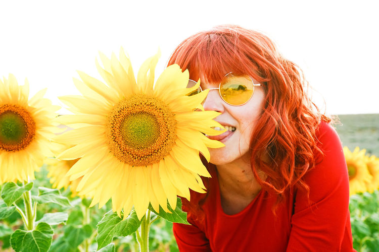 Portrait of smiling woman against sunflower