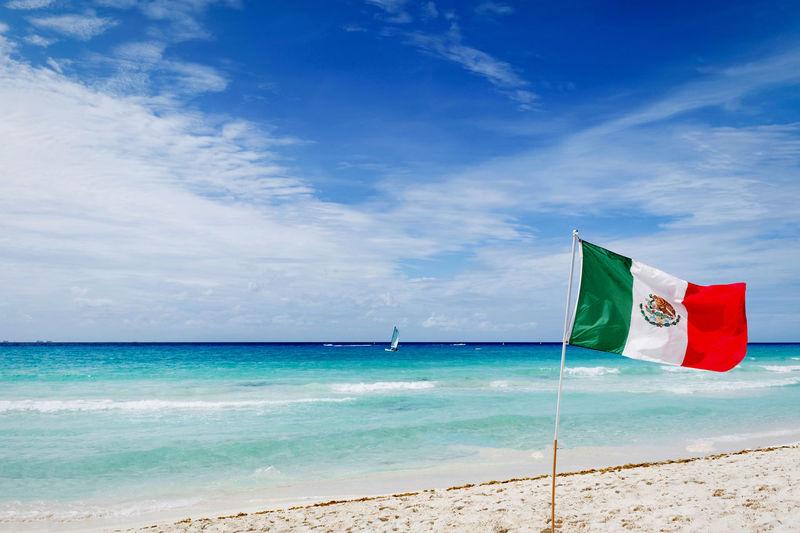 Mexican flag on beach against blue sky