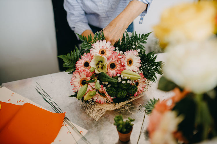 Midsection of man holding flower bouquet on table