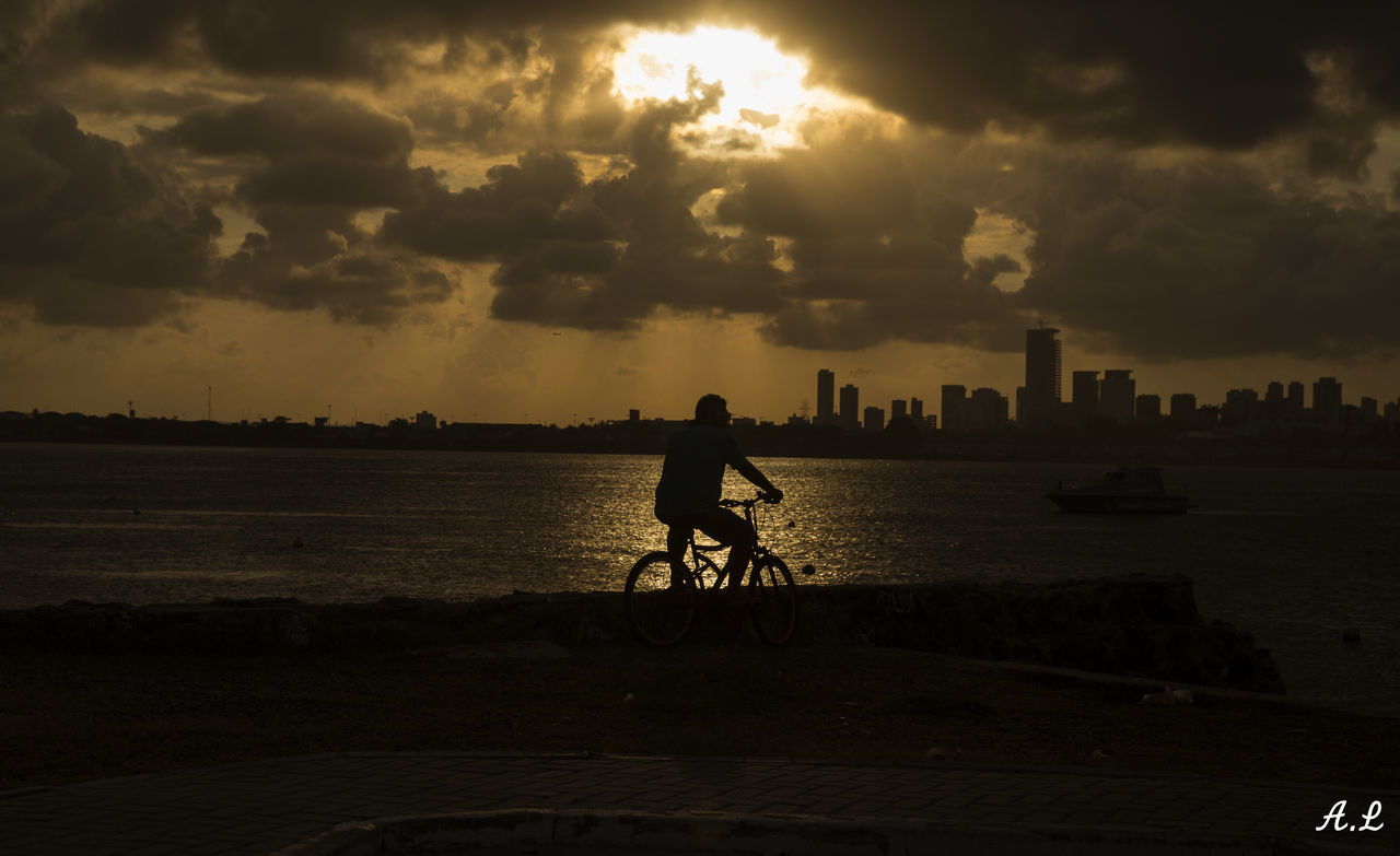 sunset, cloud - sky, sky, bicycle, silhouette, full length, one person, outdoors, real people, transportation, men, riding, water, travel destinations, architecture, city, built structure, building exterior, nature, sea, day, bmx cycling, one man only, people