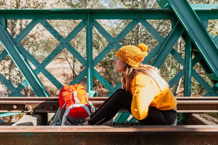 Full length of woman sitting on railing