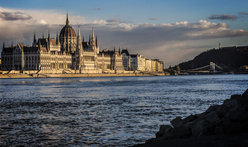 River by hungarian parliament building against sky