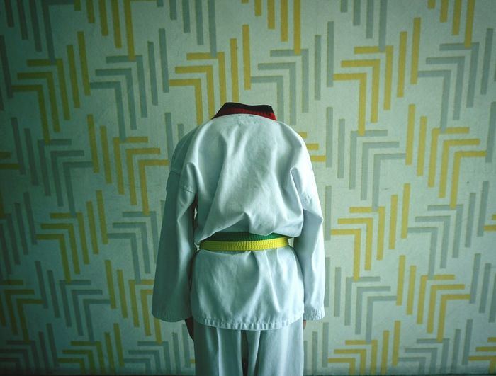 Taekwondo Boy People Man Bent Taekwondo Bow Back White Waist Level Step Green And Yellow  Computer Crime Politics And Government Police Force Men Human Back Politics Protective Workwear Rear View Standing Text Wearing
