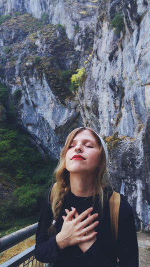 High angle view of young woman with eyes closed standing against mountain