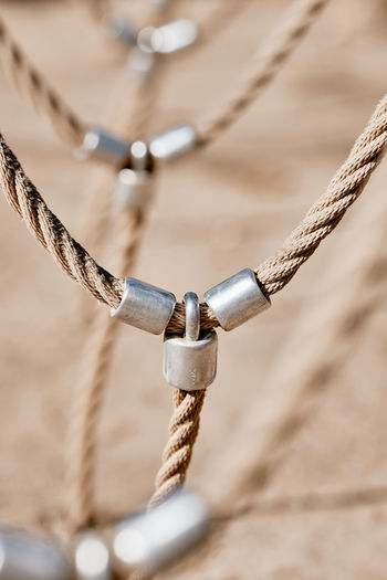 Abstract picture shot on a playground at a climbing fram with a detail with bright beige ropes connected via metal. Seen in Nuremberg, Germany, April 2019 Metal Rope Strength Connection No People Focus On Foreground Day Close-up Selective Focus Outdoors Chain Tied Up Nature Land Detail Safety Sunlight Security High Angle View Sand Outdoor Play Equipment Silver Colored Playground Abstract Pattern Textured  Texture Backgroud Calmness Tranquility Sunny Beautiful Bright Beige Colors Brown Men Iron Rope Ropes Connected Connectivity Teambuilding Strong Adventure Shaky Venture Bokeh Europe Germany Nuremberg Nürnberg Protection Skills  Diminishing Perspective