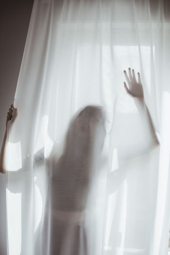 Midsection of woman standing by glass window