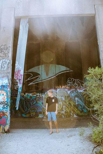 Woman standing by graffiti on wall