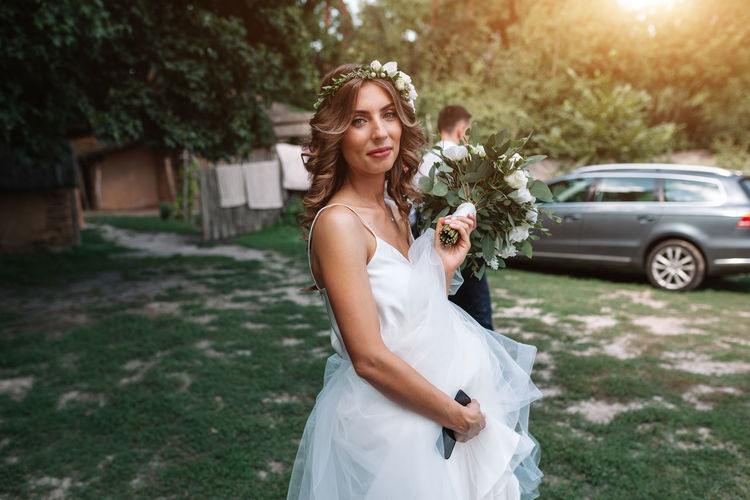 Portrait of bride holding bouquet while standing on field