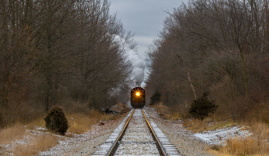 Snow covered railroad tracks by trees during winter