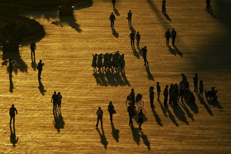 High Angle View Of People Walking On Footpath During Sunset
