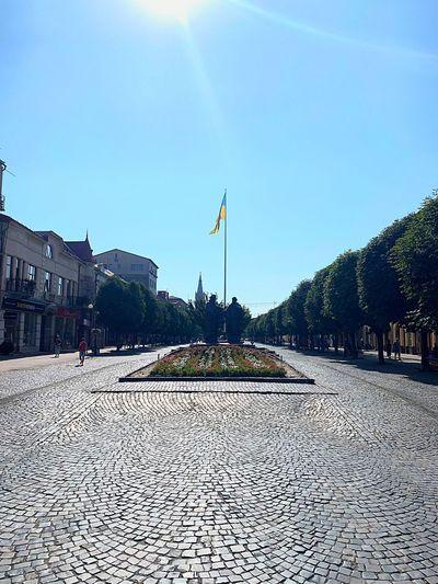 Street amidst buildings against clear blue sky on sunny day