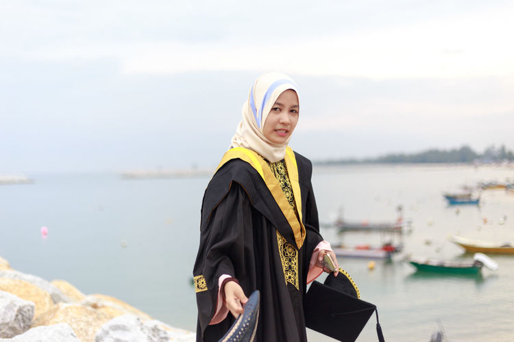 Portrait Of Young Woman In Graduation Gown Standing At Beach Against Cloudy Sky