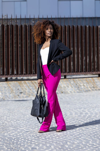 Front view of a young beautiful curly woman wearing elegant clothes and handbag while standing in the street in sunny day One Person Full Length Young Adult Real People Women Architecture Lifestyles Bag Sunlight Young Women City Day Beauty Hair Adult Curly Hair Standing Beautiful Woman Hairstyle Pink Color Fashion Outdoors Purple Woman African American Afro Denim Happiness Happy Fun Daylight Sunlight