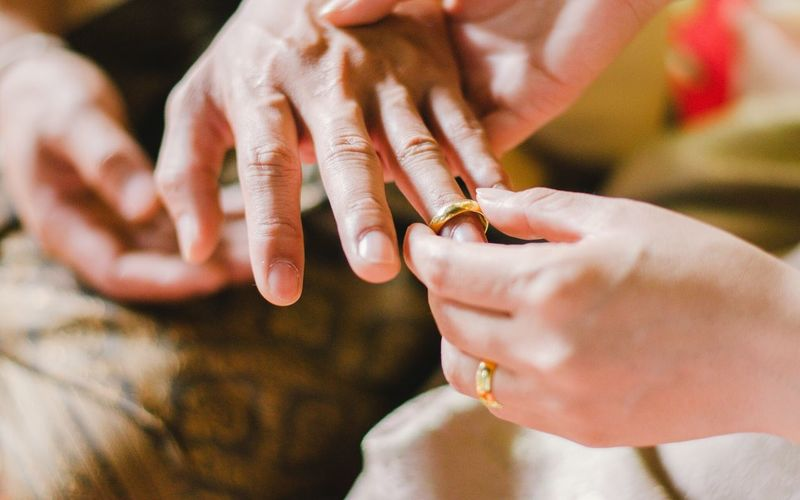 Cropped image of woman putting ring in finger of mother