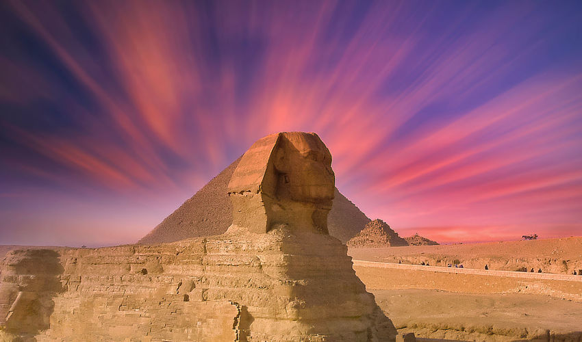 View of great sphinx and pyramid against dramatic sky