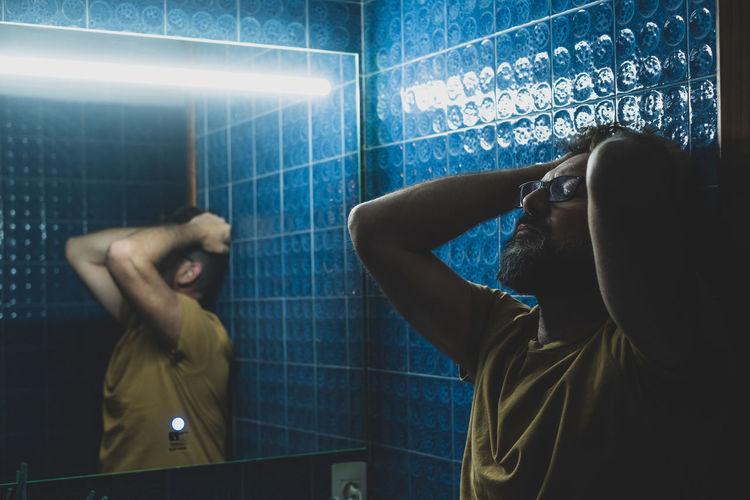 Side view of depressed man standing in bathroom
