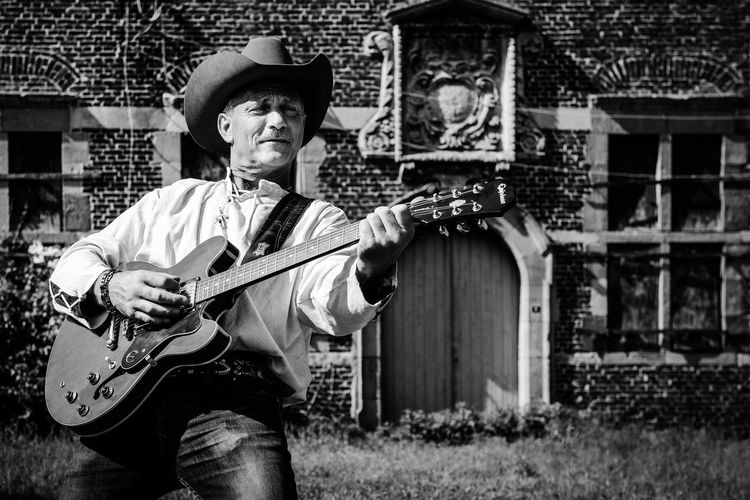 Man wearing hat playing guitar while standing against built structure