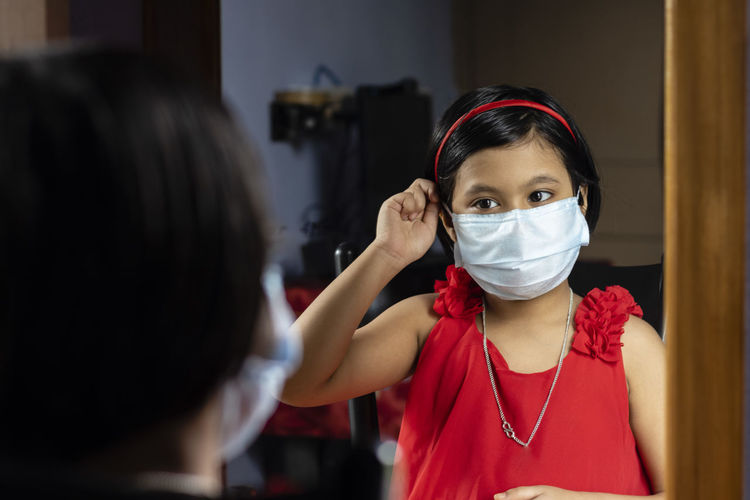 A cute indian girl child in red dress adjusting surgical nose mask in front of mirror
