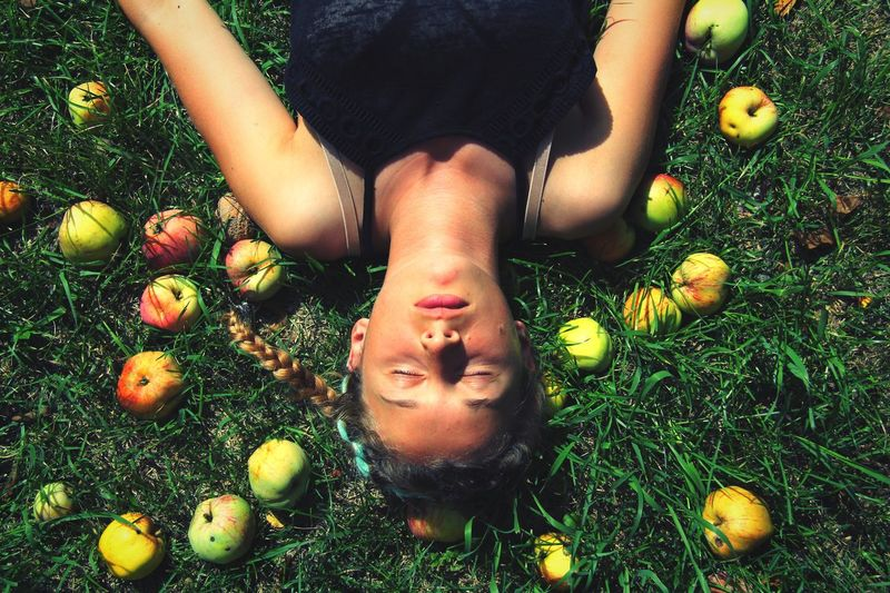 Directly Above Shot Of Young Woman Resting By Apples On Field