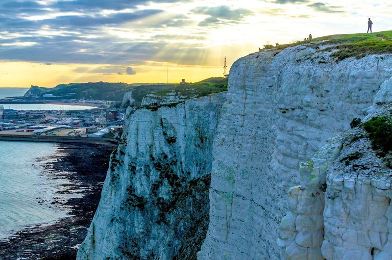 """""""Come, my friends Tis not too late to seek a newer world."""" The White Cliffs of Dover and port at sunset in Kent, on the shores of the English Channel, UK White Cliffs Of Dover Evening Light Sunset Dusk Evening Sunrise English Channel Britain Uk Kent Port Of Dover Tourism People Coastline Coast Shoreline Shore Beach Harbor Port Cliff Cliffs Chalk Cliffs Limestone Limestone Rocks Sea Nature Cloud - Sky Outdoors Sky"""