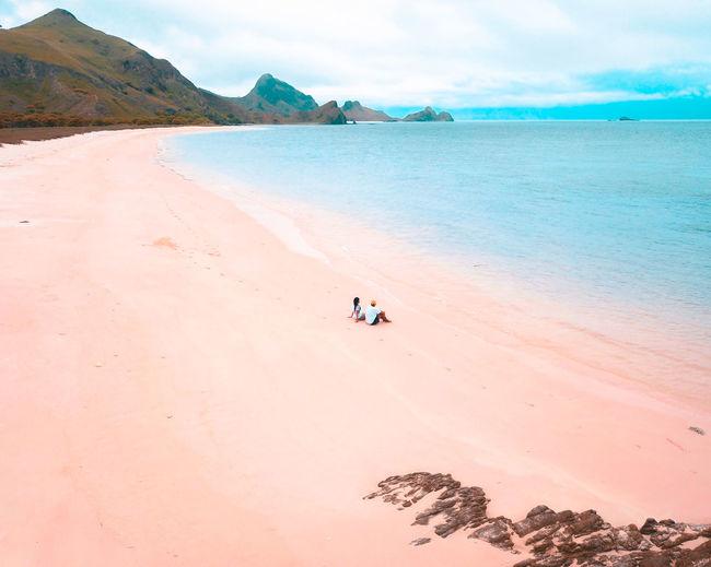 Friends sitting at beach against sky