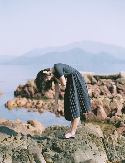 Rear view of woman standing on rock