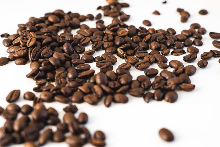 Pile of coffee beans close-up isolated on white background, with copy space Coffee - Drink Roasted Coffee Bean Large Group Of Objects Brown Coffee Food And Drink Food Indoors  Still Life White Background Freshness Close-up Roasted Coffee Bean No People Abundance Selective Focus Caffeine Drink Table Non-alcoholic Beverage