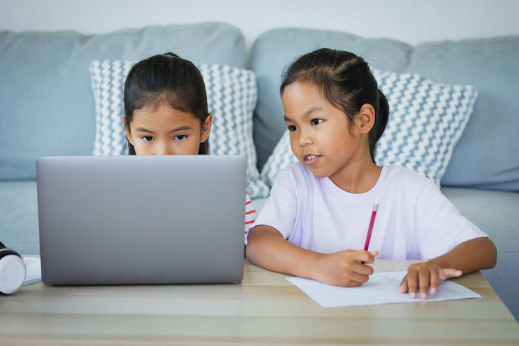 Portrait of mother and girl using laptop