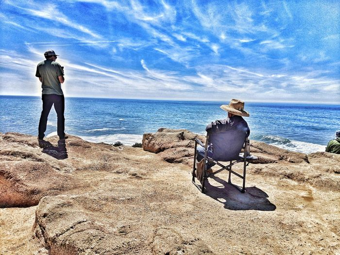Men. Ocean's cliffs edge. Whale watching. vanishing point Tourist Destination Sitting Standing Straw Hat Cap Smartphone Taking Pictures Sandstone Background Whale Watching Water Sea Full Length Men Beach Standing Shadow Sky Horizon Over Water Calm Ocean Mid Distance Countryside Tranquility Idyllic Remote Cloud Outline Headland
