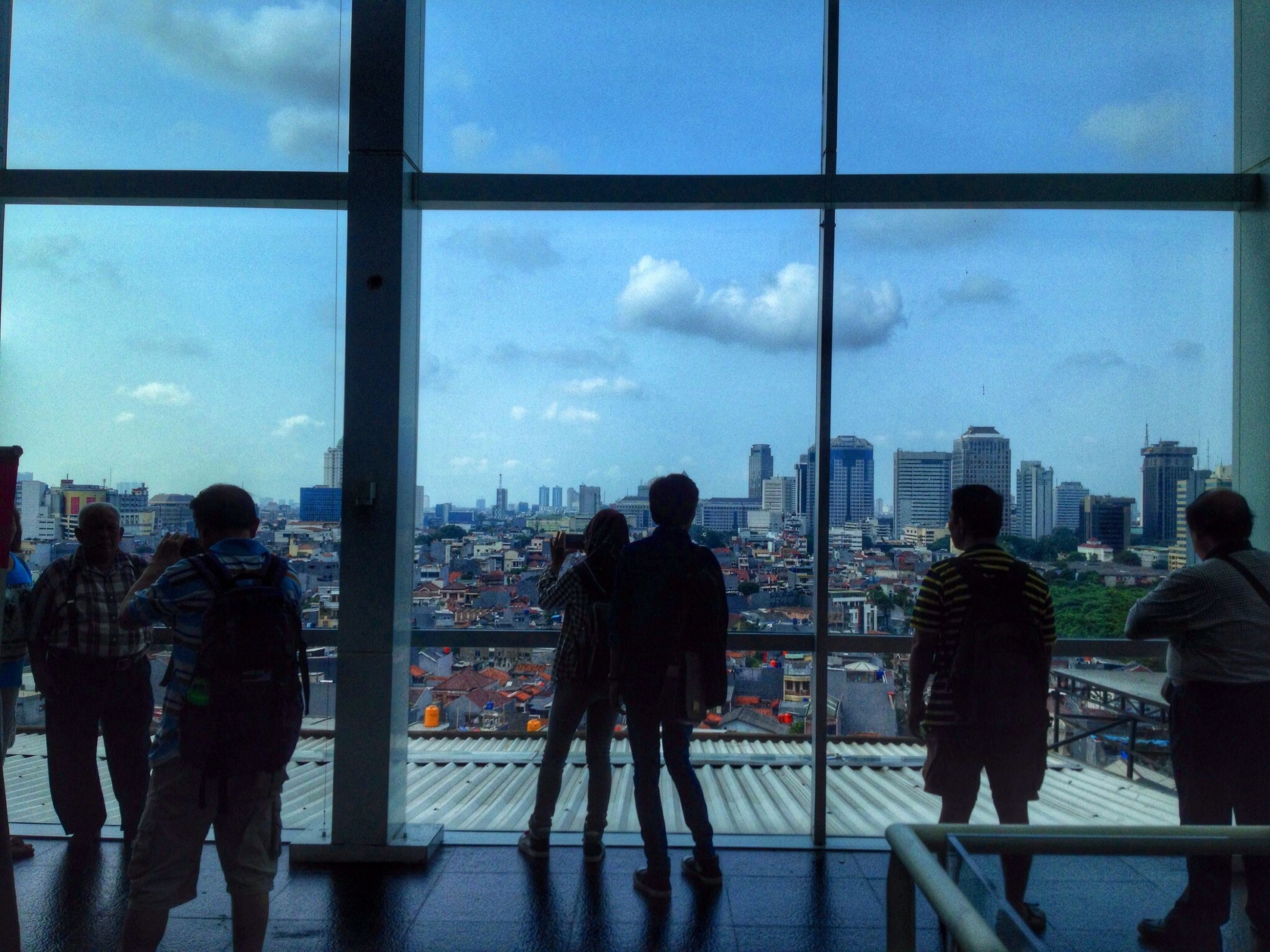 men, indoors, architecture, built structure, lifestyles, silhouette, sky, city, person, glass - material, rear view, standing, building exterior, leisure activity, cloud - sky, transparent, city life, window, togetherness