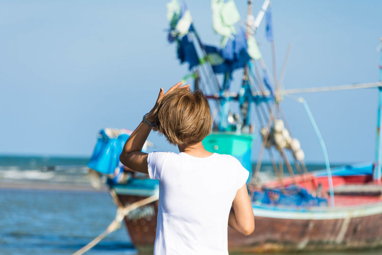 Rear view of woman on boat in sea against clear sky
