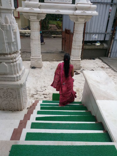 High angle view of woman moving down on steps at temple