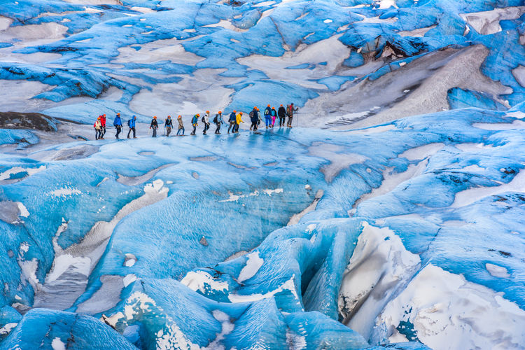 Hikers Walking On Glacier