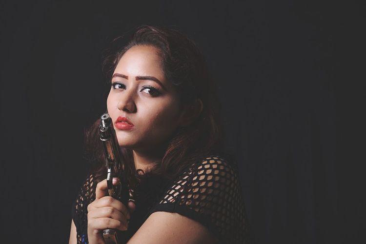 Portrait of beautiful woman holding handgun in darkroom