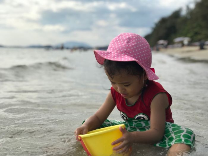 Girl playing with bucket while sitting at beach