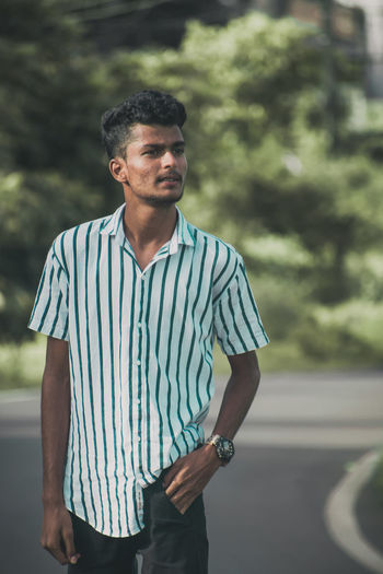 Young man standing on road
