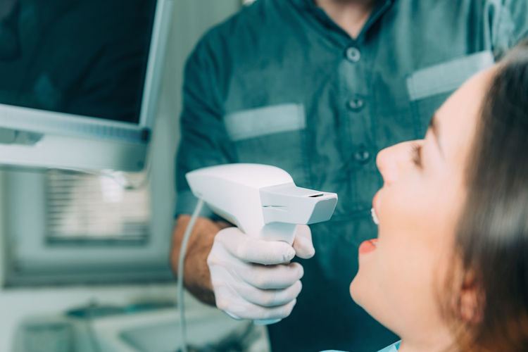 Midsection of dentist examining patient teeth