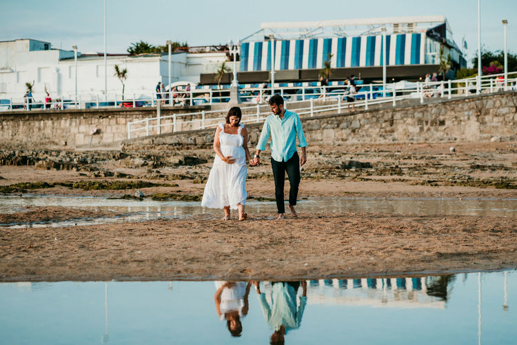 Rear view of couple walking on bridge over water